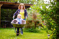 Adorable toddler boy having fun in a wheelbarrow pushing by mum in domestic garden Royalty Free Stock Photo