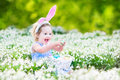 Adorable toddler girl with first white spring flowers Royalty Free Stock Photo