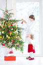 Adorable toddler girl helping her brother to decorate a beautiful Christmas tree Royalty Free Stock Photo