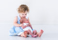 Adorable toddler girl with her newborn baby brother in a blue dress curly hair holding Stock Photography