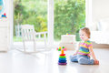 Adorable toddler girl playing with a colorful pyramis in a beaut Royalty Free Stock Photo