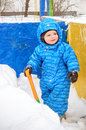 Adorable tree year old boy shoveling snow Royalty Free Stock Photo