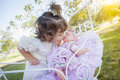Adorable young baby girl playing with baby doll and carriage her outdoors Stock Photos