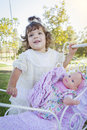 Adorable young baby girl playing with baby doll and carriage her outdoors Royalty Free Stock Photo