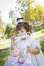 Adorable young baby girl playing with baby doll and carriage her outdoors Royalty Free Stock Image