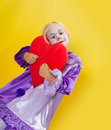 Adorable young girl clown holding a red heart for mothers day Royalty Free Stock Photo