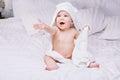 Adorable dieťa ležať na bielom uterák v posteľ