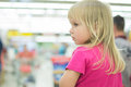 Adorble girl sit in shopping cart in supermarket Stock Photography