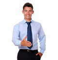 Adult businessman standing with greeting gesture a portrait of an on blue shirt while looking at you on isolated background Stock Image