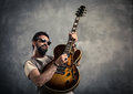 Adult caucasian guitarist portrait playing electric guitar on grunge background. Music singer modern concept Royalty Free Stock Photo