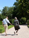 Adult couple walking older or hand in hand down a garden or park path Royalty Free Stock Photography