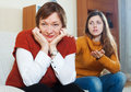Adult daughter asks for forgiveness from mature mother at home Stock Photos