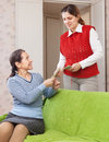 Adult daughter gives mature mother the money her at living room Royalty Free Stock Photography