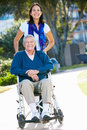 Adult Daughter Pushing Senior Father In Wheelchair Stock Photos