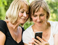 Adult daughter showing smartphone to her mature mother outdoor nature Royalty Free Stock Photos