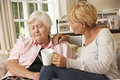 Adult daughter visiting unhappy senior mother sitting on sofa at home Royalty Free Stock Image