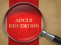 Adult education magnifying glass concept on old paper with red vertical line background Royalty Free Stock Photo