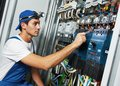 Adult electrician engineer worker young builder screwing equipment in fuse box Royalty Free Stock Image