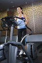 image photo : Adult female on elliptical machine.