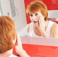 Adult female looking at wrinkles in mirror mature woman gets cream on face bathroom Stock Images