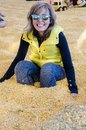 Adult female sits down in a corn pit with yellow corn kernels Royalty Free Stock Photo