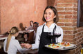 Adult female waiter showing country restaurant Royalty Free Stock Photo