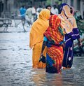 Adult females are walking in the flood water Royalty Free Stock Photo
