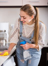 Adult girl dusting surfaces in residential kitchen cheerful russian Royalty Free Stock Photo