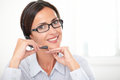 Adult girl secretary speaking on headset with spectacles while smiling and looking at you Royalty Free Stock Photo