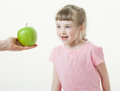 Adult hand giving a green apple for pretty little girl Royalty Free Stock Photo