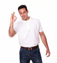 Adult hispanic man with ok sign portrait of an on white t shirt and jeans standing and looking at you on isolated studio Royalty Free Stock Photography