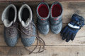 Adult and kids snow boots with gloves overhead view of a pair of standing ready on a rustic wooden floor alongside a pair if Royalty Free Stock Image