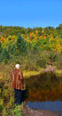 Adult male stands front pool abandoned road road leads to cliff copper mine upper penninsula michigan autumn color reflects pool Stock Image