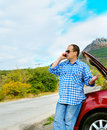 Adult man is calling to support standing beside broken car Royalty Free Stock Photo