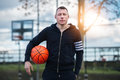 Adult man holding basketball ball standing on street basketball playground at sunset time Royalty Free Stock Photo