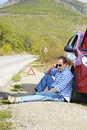 Adult man is sitting near his broken car waiting for tow Royalty Free Stock Photo