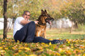 Adult man sitting outdoors with his german shepherd llying down pet dog Stock Images