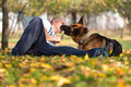 Adult man sitting outdoors with his german shepherd llying down pet dog Stock Photos
