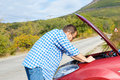 Adult man is standing near his broken car waiting for tow Stock Images