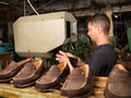 Adult man working in a shoe factory Stock Images
