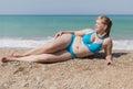 Adult plump woman in blue bikini lying on pebble Royalty Free Stock Photo