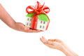 Adult s hand giving child s hands a model of the house are at white background Royalty Free Stock Images