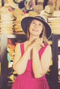 Adult smiling woman try on boater hat  in shopping mall Royalty Free Stock Photo