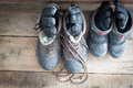 Adult snow boots alongside those of a child view from above pair on the wooden floor cabin each with pair gloves Stock Photography