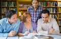 Adult students studying together in the library four mature Royalty Free Stock Photos