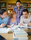 Adult students studying together in the library four mature Stock Photography