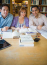 Adult students studying together in the library portrait of three mature Stock Photo