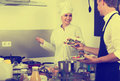 Adult woman cook giving salad to waitress Royalty Free Stock Photo