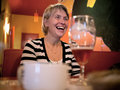 Adult woman laughs in a cafe on the background of glass Royalty Free Stock Image