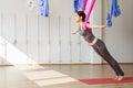 Adult woman practices aero anti-gravity yoga position in studio